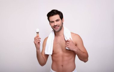 Smiling muscular guy with a white shower towel.