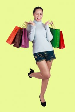 Shopping woman holding shopping bags  on green background . Beau