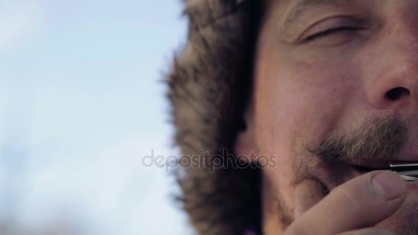 Egy ember, játszik egy hárfa portréja. A szakállas sámán játszik a harmonika drymba. Közelkép a zenész doromb szembe. Arc közelről, egy hangszer, doromb.