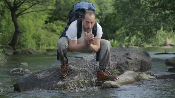 Guy vousatý muž cestuje podél řeky ford. Turistický batoh přes řeku. Vousatý chlap přes řeku