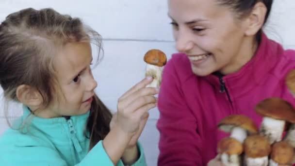 Mutter und Tochter säubern frisch gepflückte Pilze. Porträt einer Mutter mit ihrem Kind bei der Reinigung ökologisch sauberer Lebensmittel. Essen, Kochen, Umweltfreundlichkeit.