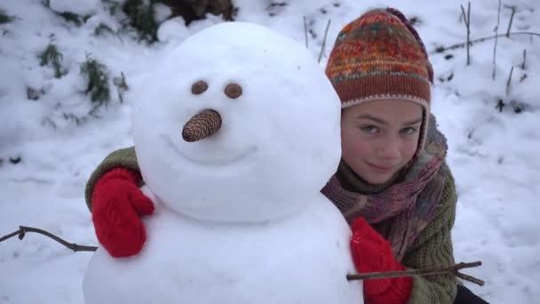A fiú az épület egy kertben hóember. Egy gyerek a télen a parkban sculpts egy hóember.