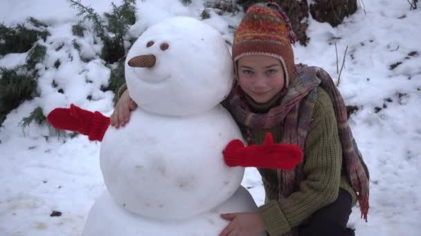 Chlapec je stavění sněhuláka v zahradě. Dítě v zimě v parku modeluje sněhulák.