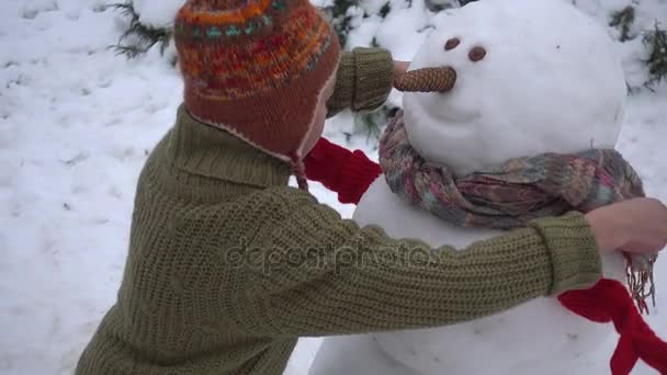 The boy is building a snowman in the garden. A child in the winter in the park sculpts a snowman.