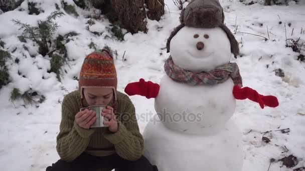 Egy fiú iszik teát közelében egy hóember, télen az utcán. A gyermek a teázás egy hóember a kertben.