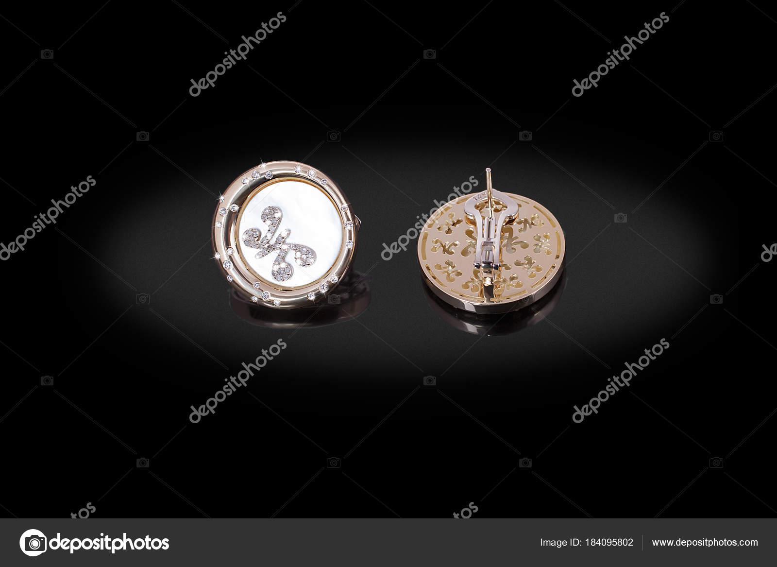2be34a12b911 Redondeos oro preciosos pendientes con nácar de diamantes y mariposa sobre  fondo negro — Foto de