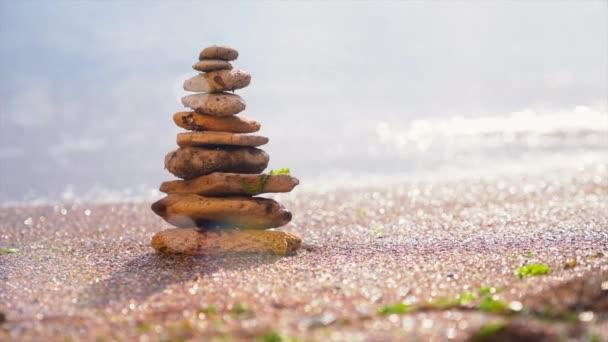 Kamenná pyramida na písku symbolizující zen, harmonii, rovnováhu. Pozitivní energie. Oceán v pozadí