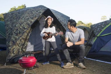 Father and daughter at camping playing ukulele