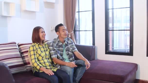 Happy asijské ženy a muži sledují televizi doma