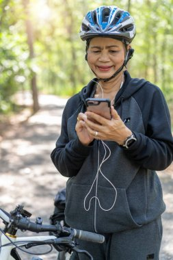 Senior asian woman bicycle in the park, With using smart phone a
