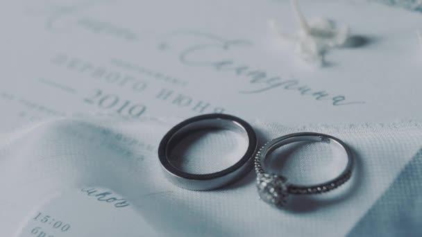 Fehér arany gyűrűk fekszenek egy meghívón.