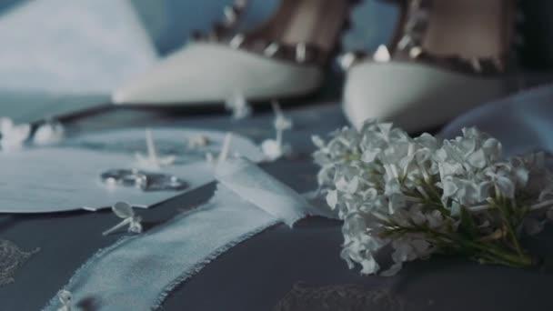 Svatební boty a karty s kroužky leží na posteli.