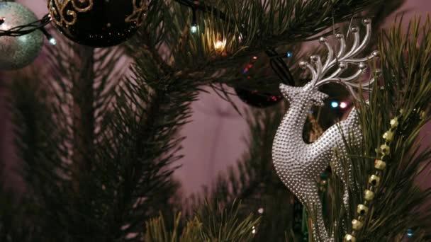 A játék egy zöld karácsonyfán lóg. Újévi ajándékok Karácsonyi és újévi ünnepség. Karácsonyi jelenet. Karácsonyi ajándékok a karácsonyfa alatt.