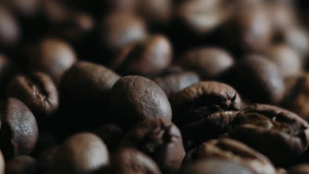 Tmavá kávová zrnka. Točí se a padá. Kávová zrna. Zavřete semínka kávy. Krásná semínka kávy.