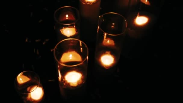 Rows of hundreds burning votive candles in dark moody sacral environment, background texture, shallow depth of focus, light bokeh effect. Memory and prayer, contemplation, church small candles concept