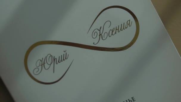 Wedding rings near invitation envelopes and perfume boxes