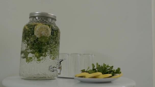 hatalmas üveg egy csapot, amelyben limonádé van az asztalon szemüveggel