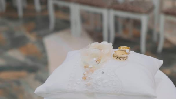 Wedding rings on a white pillow. The concept of wedding events-two gold rings on a bow of ribbon.