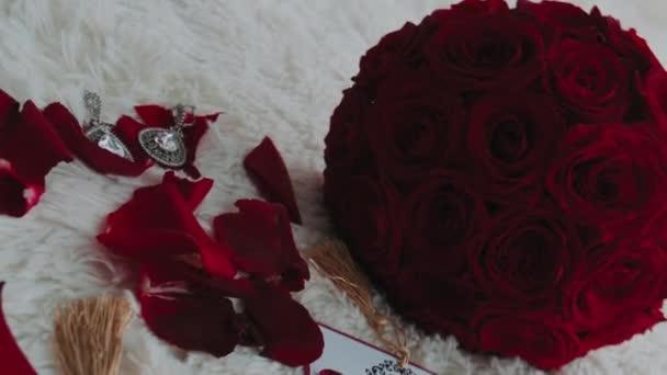 Egy csokor vörös rózsa és üdvözlőkártya fekszik az ágyon Valentin-napra. Ajándékok Valentin-napra.