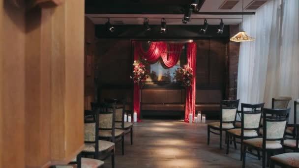 červený oblouk pro registraci stojany v místnosti zdobené květinami a svíčky v blízkosti jsou ve dvou řadách mnoho židlí