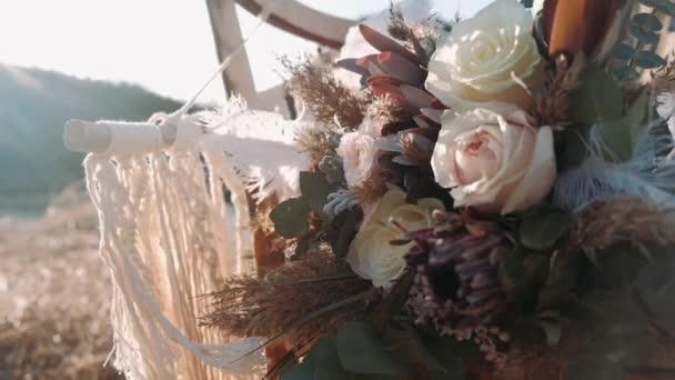 Boho esküvői csokor Egy nagy fehér toll egy csokorban ringatózik a szélben. Boho esküvői csokor fekszik egy szék a természetben