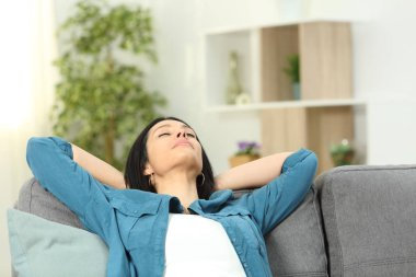 Relaxed woman resting with arms on head sitting on a sofa at home