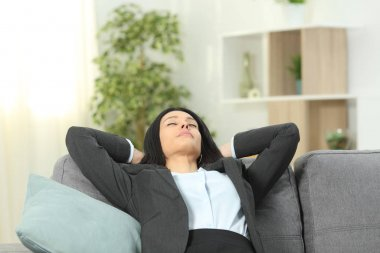 Office worker rests after work sitting on a couch in the living room at home