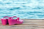 Opuštěné sandály na dřevěné palubě na pláži