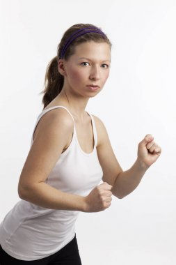 young woman with a determined gaze and upheld fists