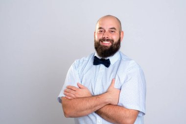 young smiling and bearded man in blue shirt and bow tie