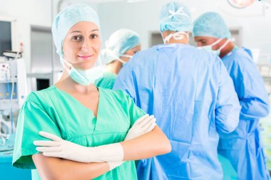 Hospital - surgery team in the operating room or Op of a clinic operating on a patient in emergency