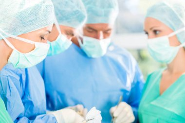 Hospital - surgery team in the operating room or Op of a clinic operating on a patient, perhaps it's an emergency a assistant holding a cotton swap forceps
