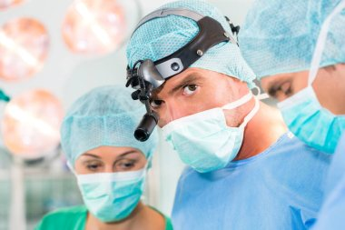 Hospital - surgery team in the operating room or Op of clinic operating on patient in an emergency situation