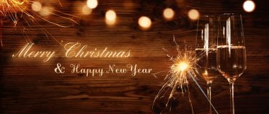 Christmas and New years card with champagne and sparkler in front of rustic wood and golden bokeh for greetings