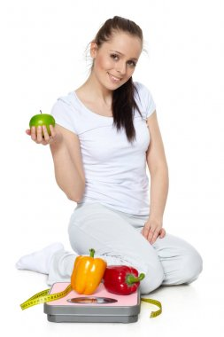 Sporty young woman with scales, fresh peppers and apple on a white background.  Concept of healthy lifestyle.