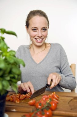 Young woman standing at a kitchen counter slicing fresh tomatoes with a large chefs knife smiling as she works
