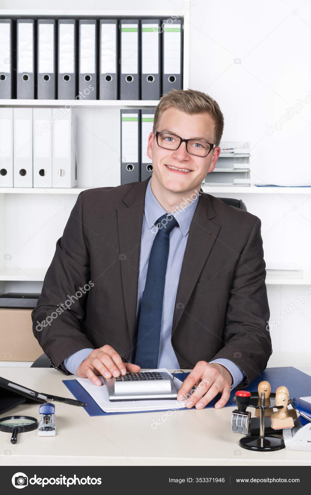 Jungunternehmer Mit Brille Sitzt Schreibtisch Buro Und Rechnet Mit Einem Stockfoto C Panthermediaseller 353371946