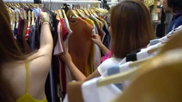 női barátok kiválasztása ruhák plázában, vásárlási koncepció