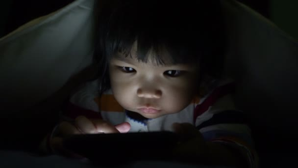 cute little Asian girl playing on smartphone while lying in bed