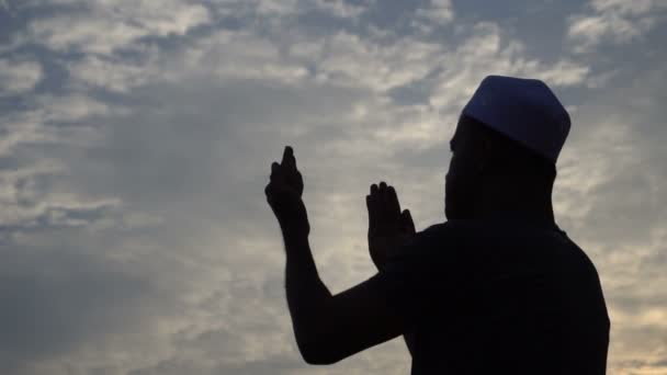 Young Asian muslim man praying at sunset