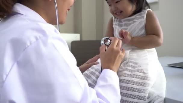 Asiatischer Arzt mit einem Stethoskop, um Atmung und Herz eines schönen Mädchens zu überprüfen