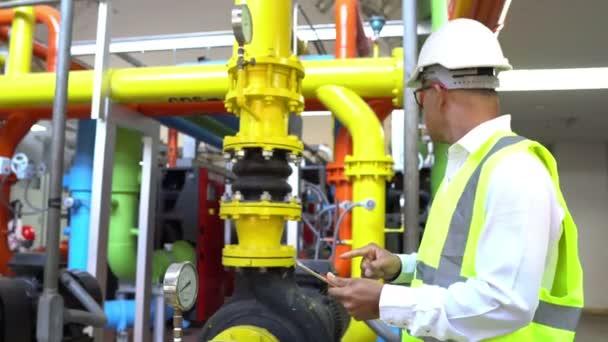asiatischer Wartungsingenieur im Abwassermanagementsystem einer riesigen Fabrik, der technische Daten von Heizungsanlagen überprüft, thailändische Mitarbeiter