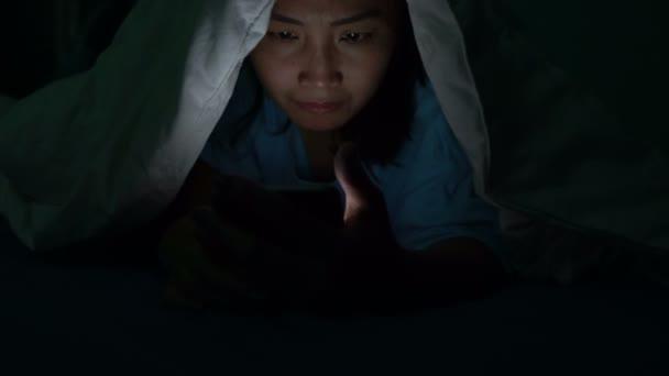 Asiatin spielt nachts auf Smartphone im Bett