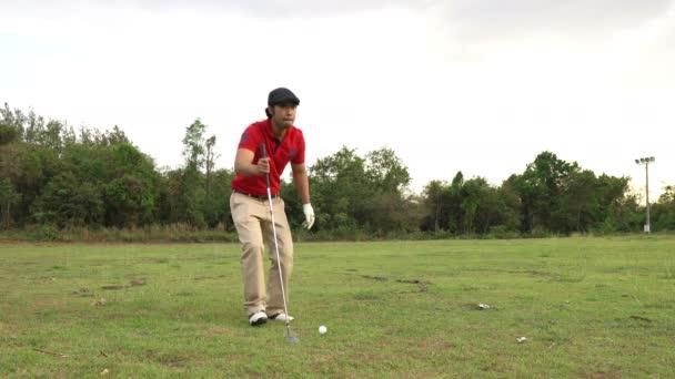 Asijský golfista hraje golf v jasný letní den, sportovní koncept
