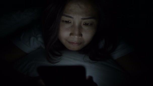 asiatische Frau spielen Smartphone in das Bett in der Nacht, thailändische Menschen