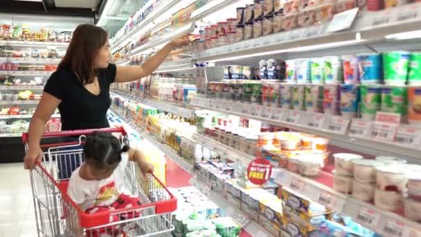 Matka a roztomilá dcera výběr produktů v supermarketu