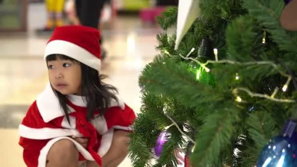 Porträt von süßen asiatischen Mädchen mit Weihnachtsmütze posiert in der Nähe des Weihnachtsbaums