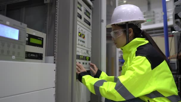 Electrical engineer woman checking voltage at Power Distribution Cabinet in control room