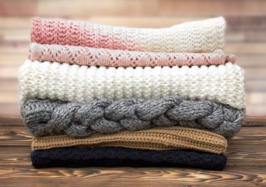 Winter knitted clothes stack on wooden background.