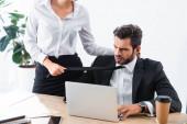 Üzletasszony húzza üzletember nyakkendő a munkahelyen